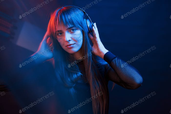 Good mood for all. Studio shot in dark studio with neon light. Portrait of young girl