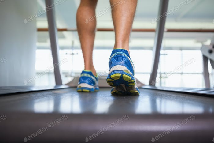 Rückansicht tiefer Abschnitt eines Mannes läuft auf Laufband in der Turnhalle