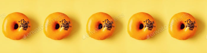 Flat lay donuts pattern on pastel orange background. Top view. Square crop. Sweet doughnut texture