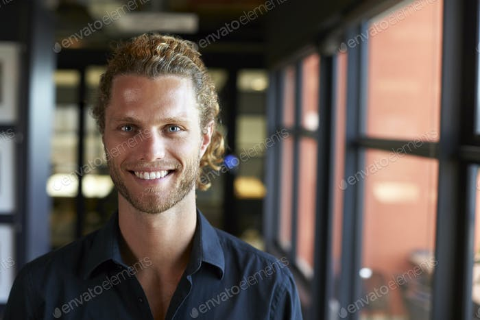 Millennial white male business creative smiling to camera by the window in an office, close up