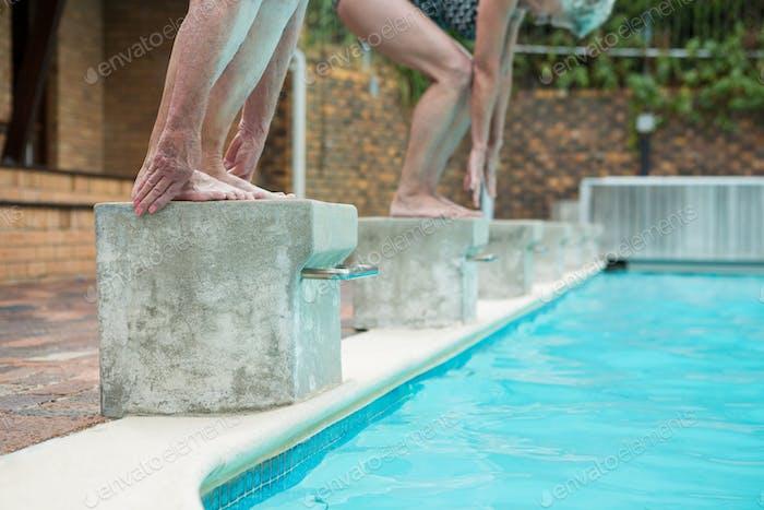 Two senior women preparing to dive in pool