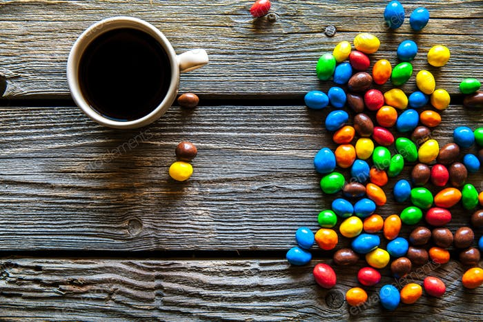 colored sweets with coffee on a wooden background