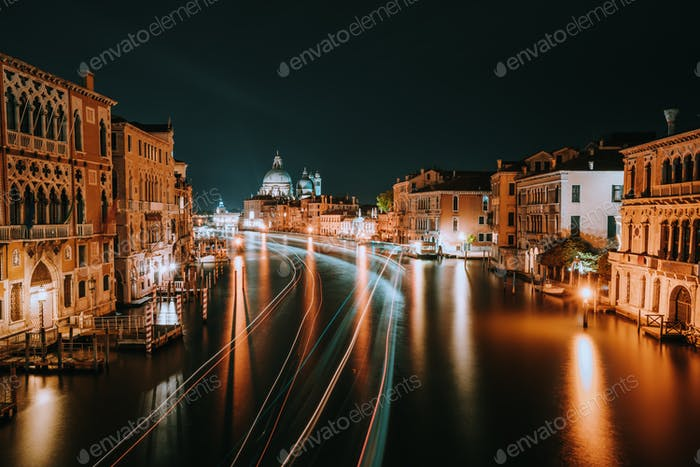 Venice night scenery. Light illuminated trails of ferries and boats reflected on the Grand Canal