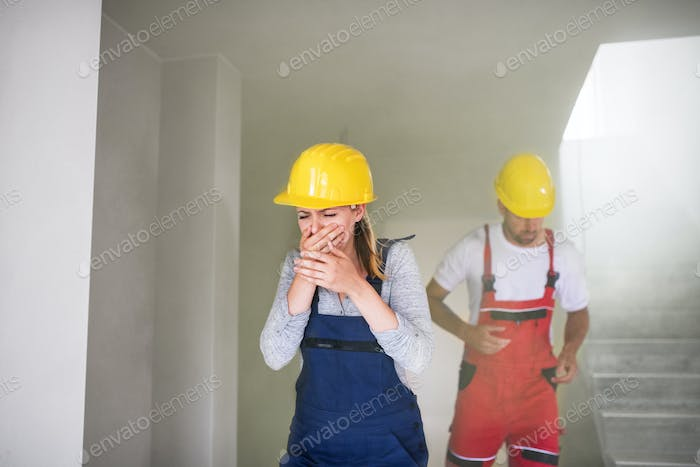 Woman and man workers running from the construction site, coughing.