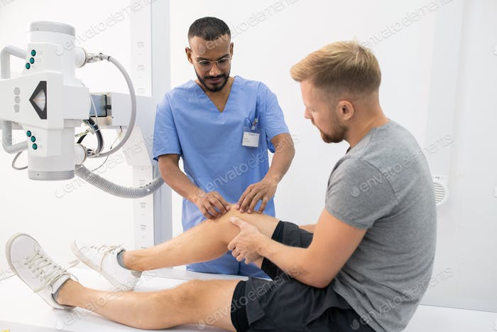 Contemporary clinician in uniform massaging sick knee of young man in hospital