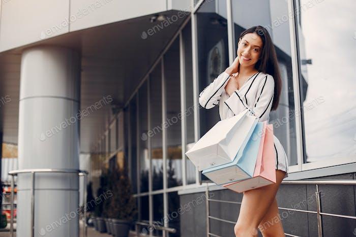 Niedliches Mädchen mit Einkaufstasche in einer Stadt