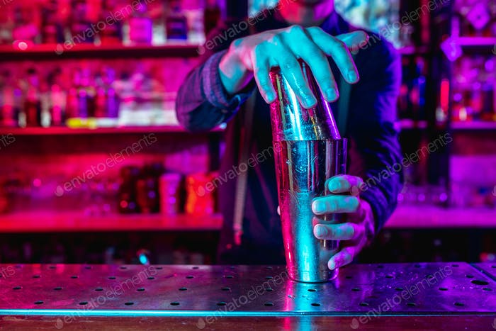 Close up of barman finishes preparation of alcoholic cocktail with shaker in multicolored neon light