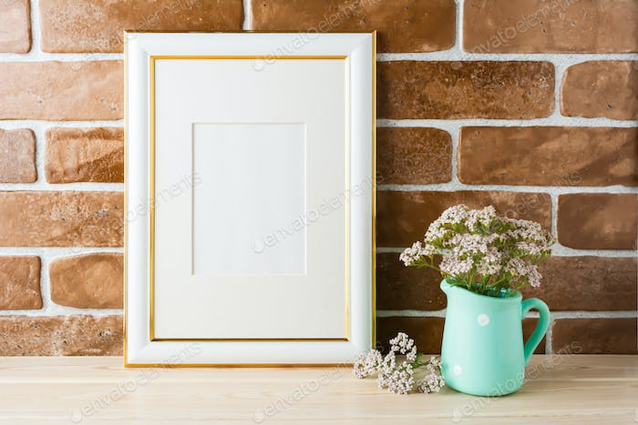 Gold decorated frame mockup soft pink flowers exposed brick wall