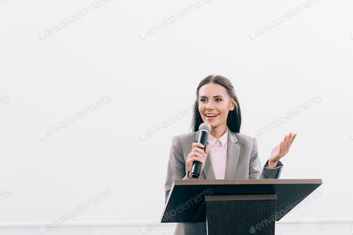 attractive smiling lecturer talking into microphone and gesturing at podium tribune during seminar