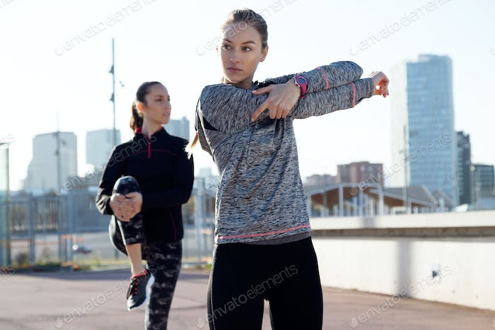 Two fit and sporty young women doing stretching in city.
