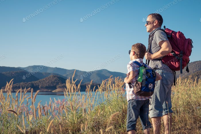 Happy family standing near the lake at the day time.