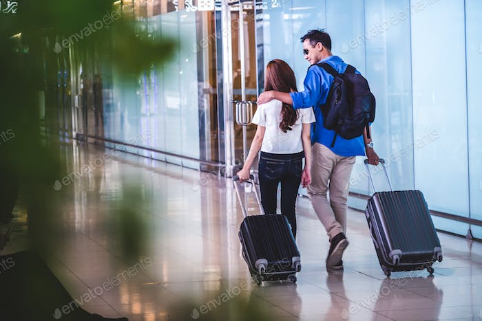 Asian couple traveler walking with suitcases in modern an airport