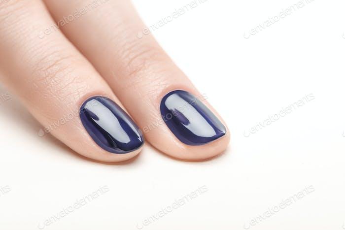 Fingernägel mit glänzendem marineblauem Nagellack auf weißem Hintergrund