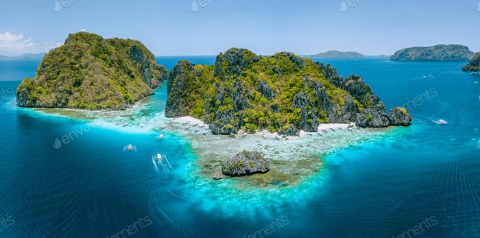 Aerial drone view of tropical Shimizu Island steep rocks and white sand beach in blue water El Nido