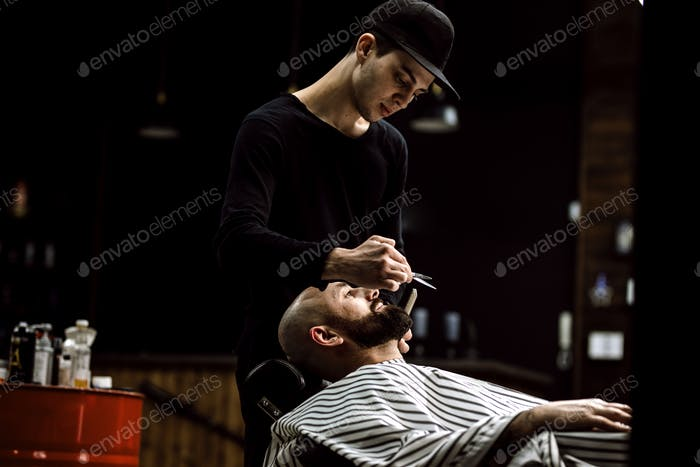Men's style. The barber dressed in a black clothes scissors beard of brutal man in the stylish
