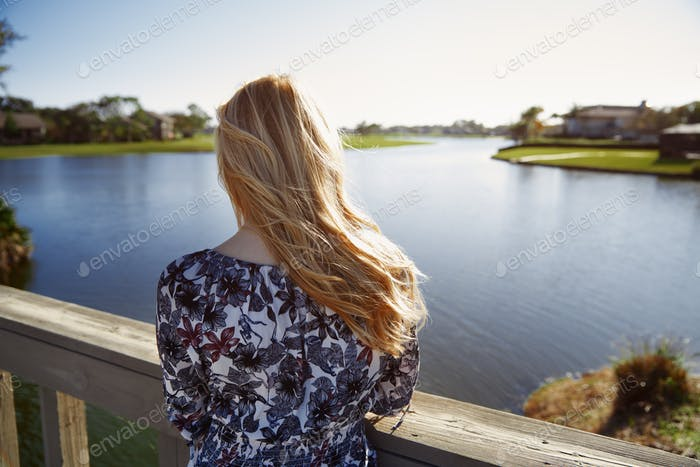 Retro styled woman standing on the wooden bridge and looking at the lake