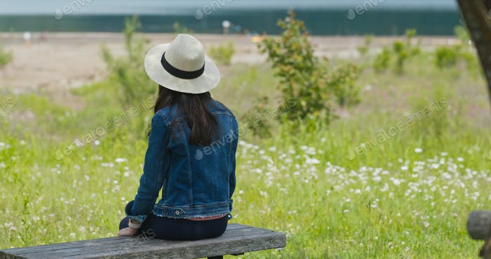 Woman look around and sit on the wooden bench