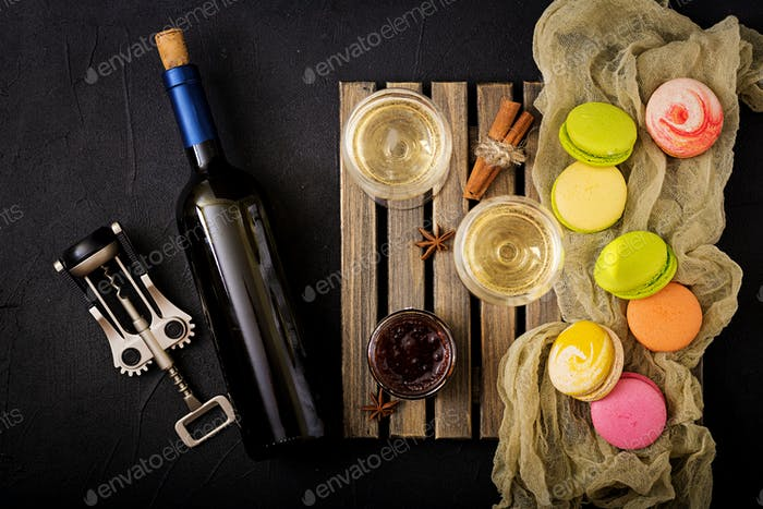 Bottle of dry white wine and a macaroon. Flat lay. Top view.