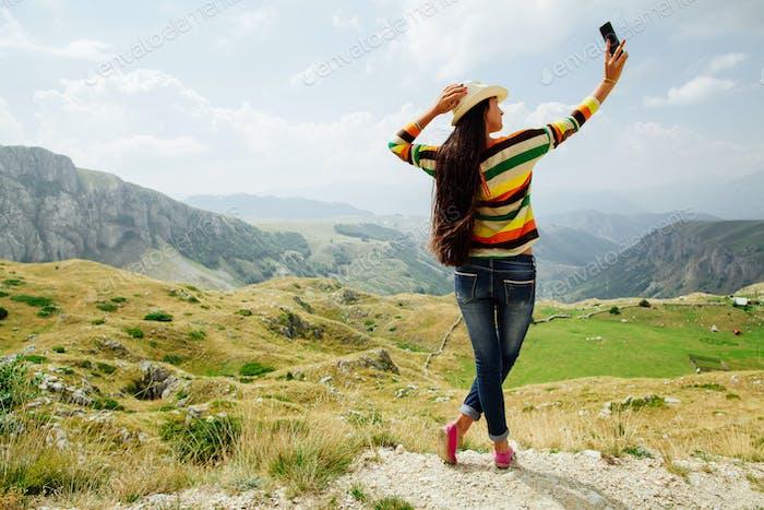 selfie Foto lange Haare Mädchen nehmen auf Smartphone in Bergdorf