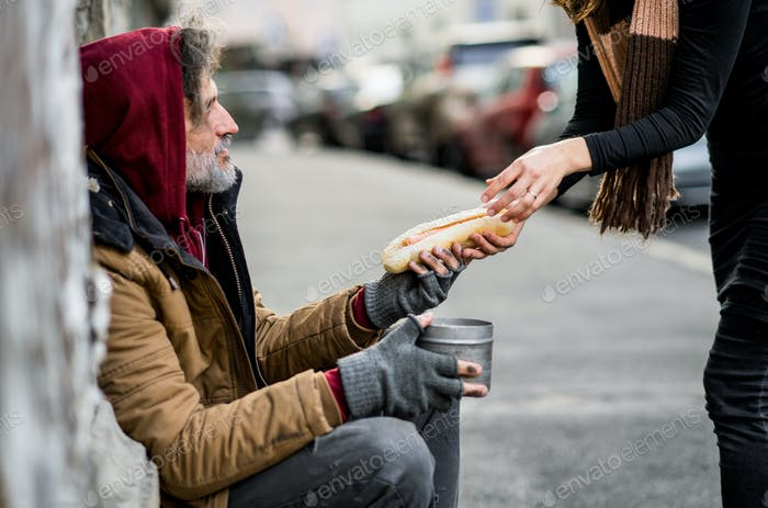Unrecognizable woman giving food to homeless beggar man sitting in city.
