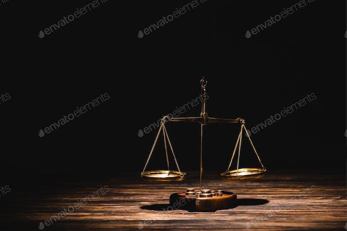 escamas doradas de la justicia sobre mesa de madera sobre fondo negro
