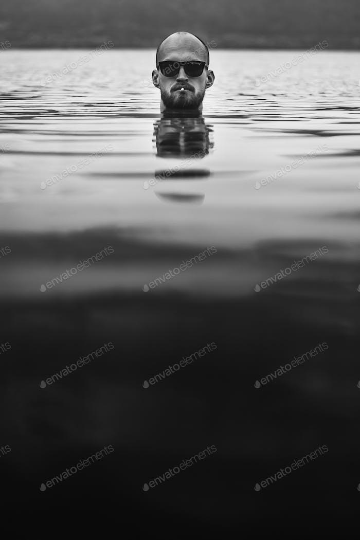 Brutal bärtiger Mann mit Zigarette und Sonnenbrille entstehen im See
