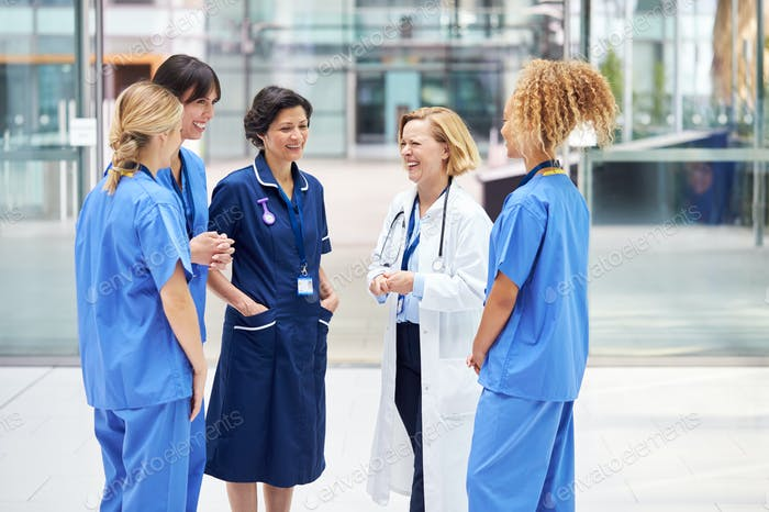 Female Medical Team Having Informal Meeting Standing In Lobby Of Modern Hospital Building