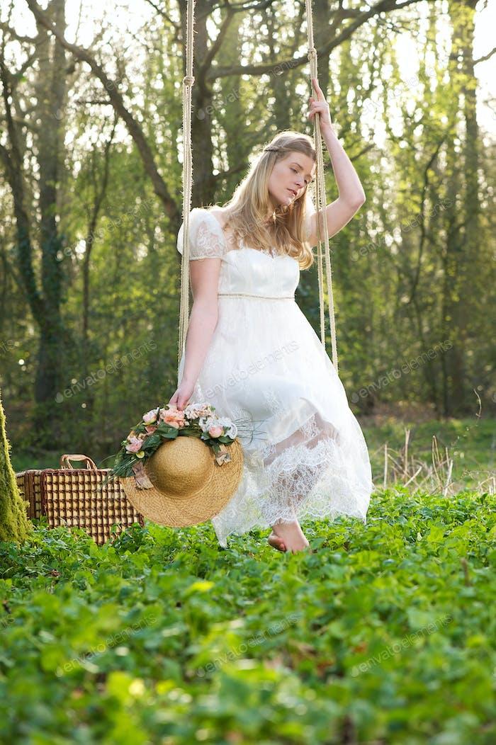 Junge Frau in weißem Kleid sitzt auf einer Schaukel im Freien