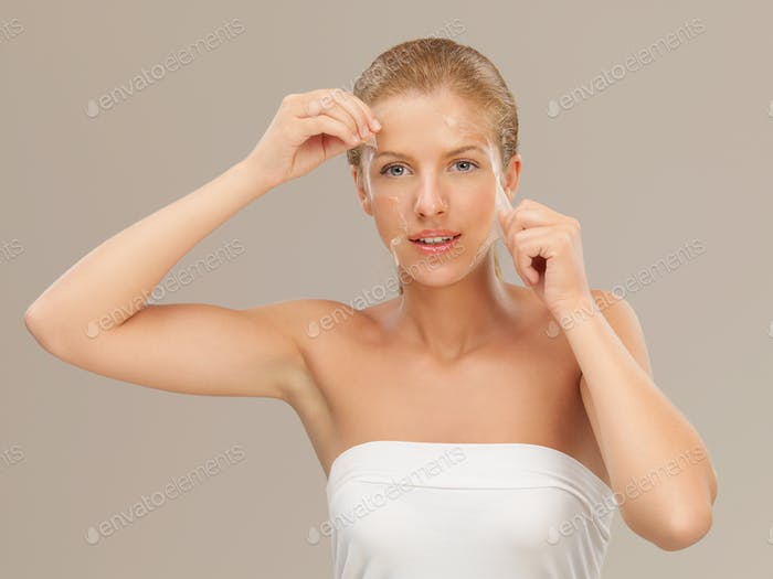 young woman peeling off a facial mask smiling