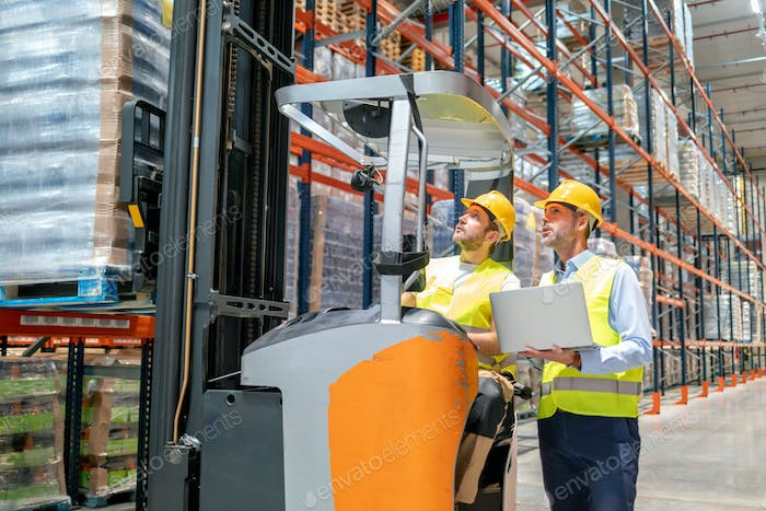 Worker using forklift and talking with his manager in large warehouse