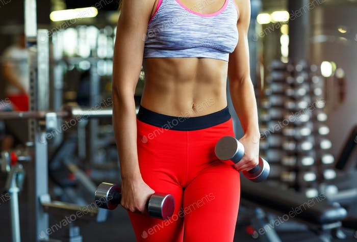 Slim woman with dumbbell in the gym doing exercises