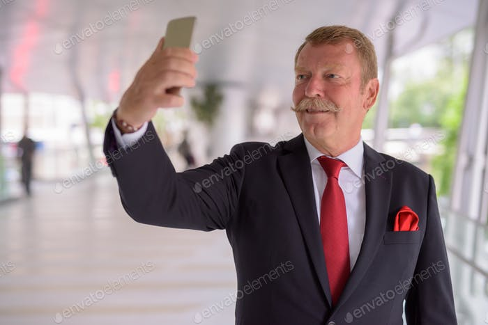 Handsome senior businessman with mustache taking selfie in the city