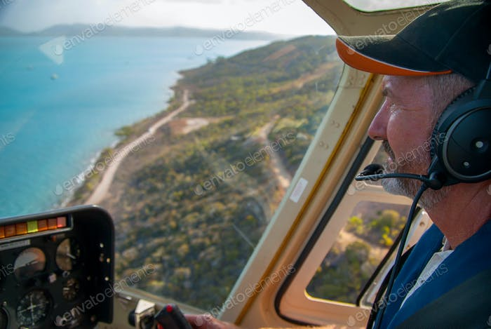Mature helicopter pilot in the cabin during the flight over the island and ocean