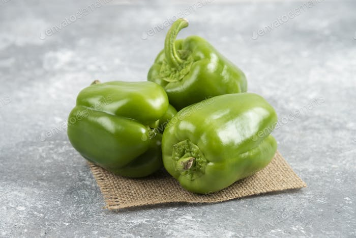 Green bell peppers on a piece of burlap