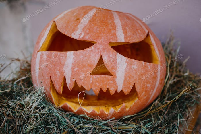 Carved pumpkin with scary face on hay bale, modern festive decoration