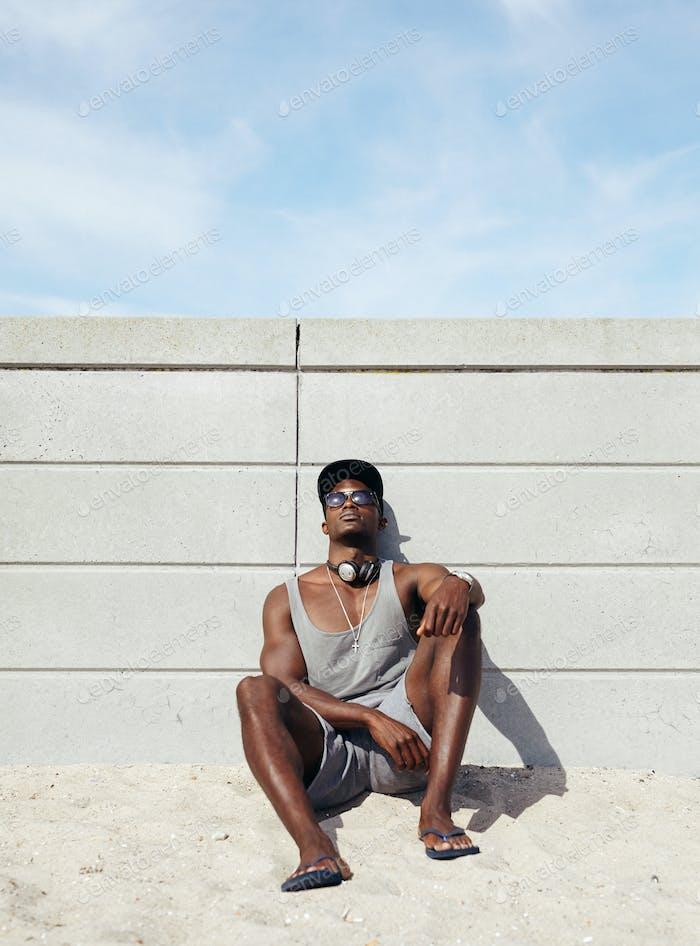 Junger afrikanischer Mann entspannt am Strand.