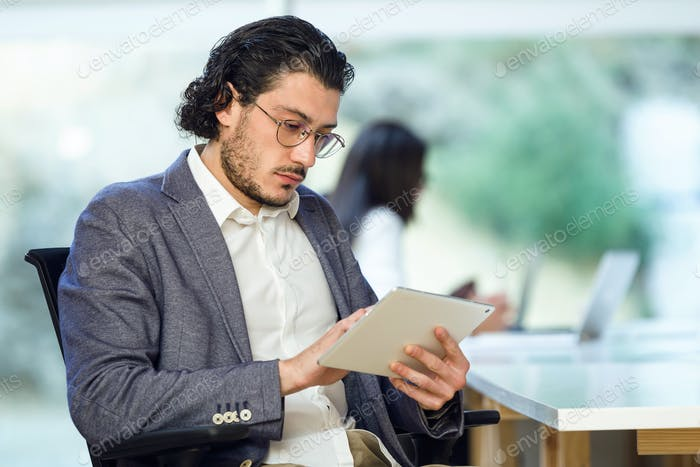 Confident young businessman working with his digital tablet on c