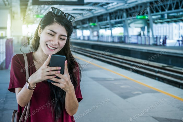 Asian woman passenger with casual suit using the social network via smart mobile phone