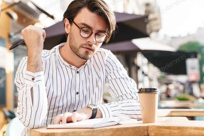 Photo of serious unshaven man wearing eyeglasses writing on diary and drinking coffee