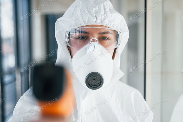 Female doctor scientist in lab coat, defensive eyewear and mask standing indoors