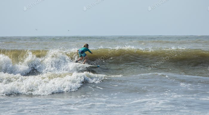 Panorama of young boy surfing on the Atlantic Ocean.