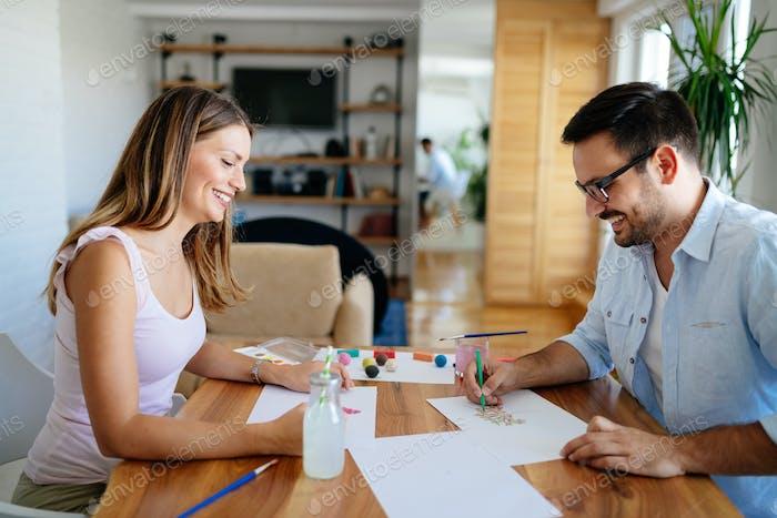 Happy couple having fun drawing at home