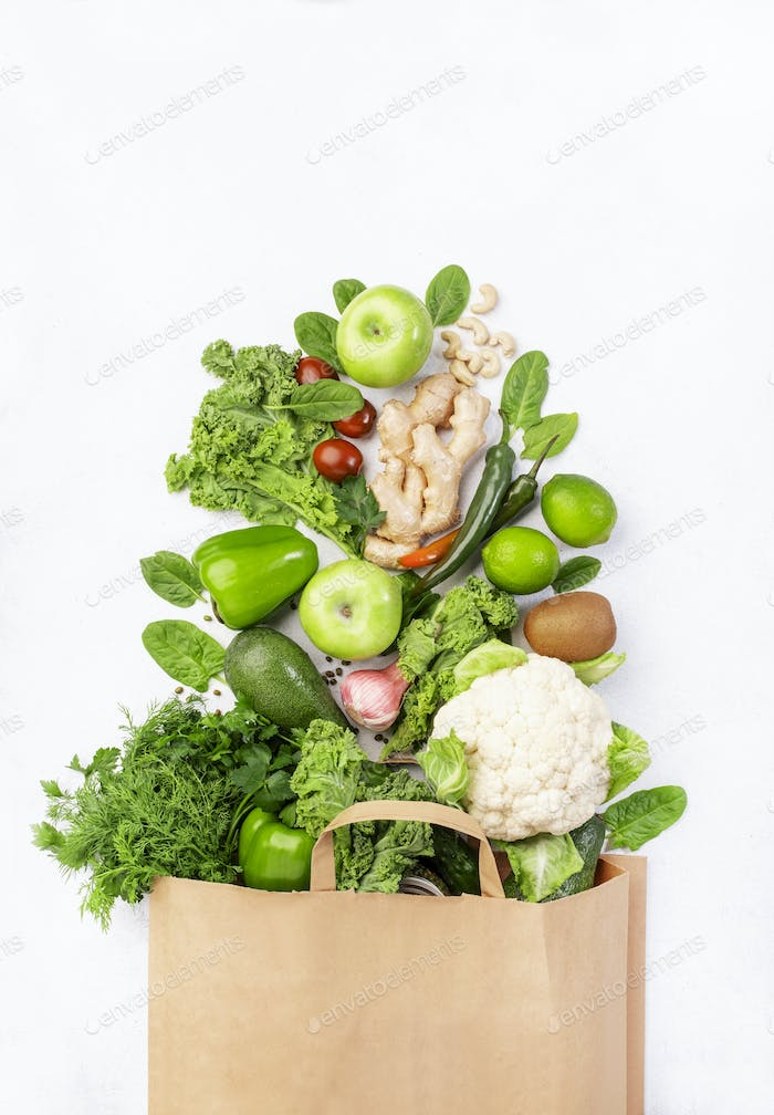 Healthy green vegan vegetarian food in full paper bag, vegetables and fruits on white