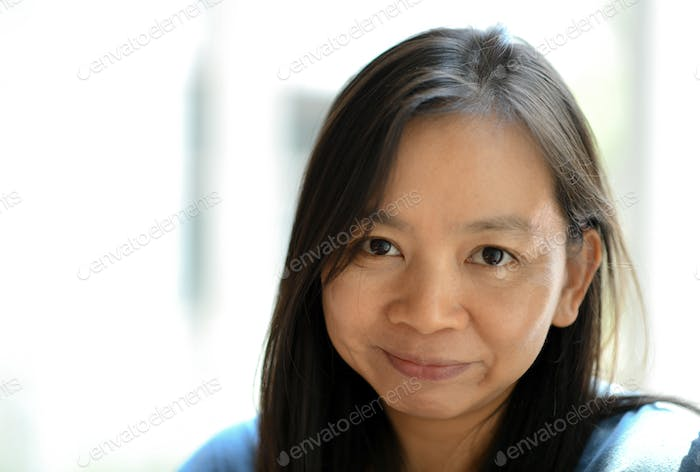Portrait asian woman,She smiles and has natural facial wrinkles.