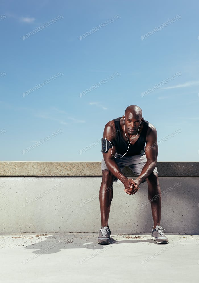 Fit young man taking rest after running workout