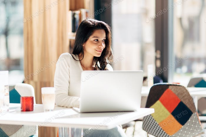 Beautiful young cute brunette studying on notebook