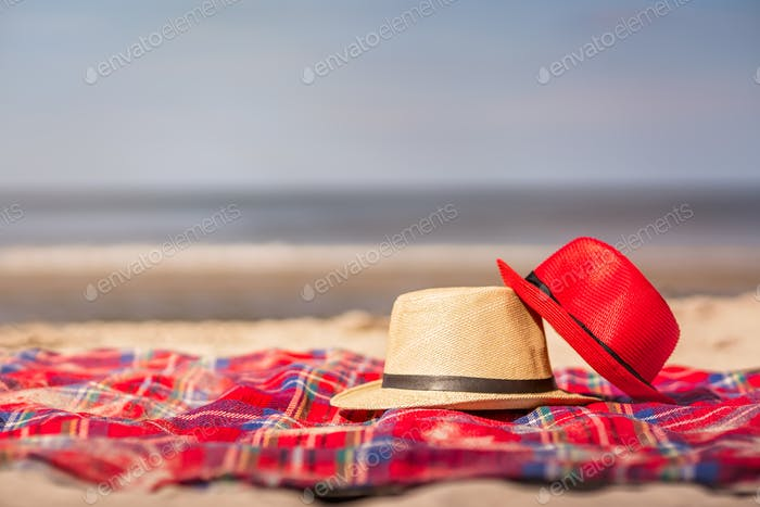 Red and white straw hats on the colorful blanket on the  beach