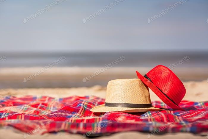 Rote und weiße Strohhüte auf der bunten Decke auf der Strand