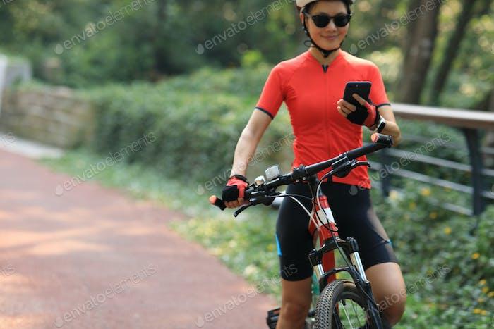 Frau Biker mit Smartphone mit Fahrrad im Park