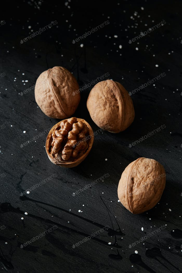 Walnuts and kernels on a black rustic backdrop